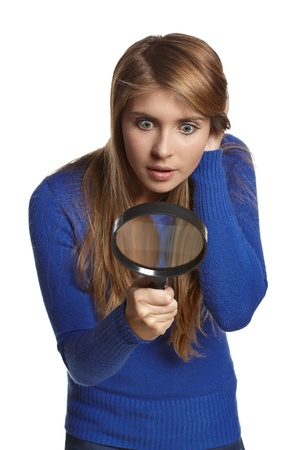Astonished girl looking through the magnifying glass downwards, over white background Reklamní fotografie