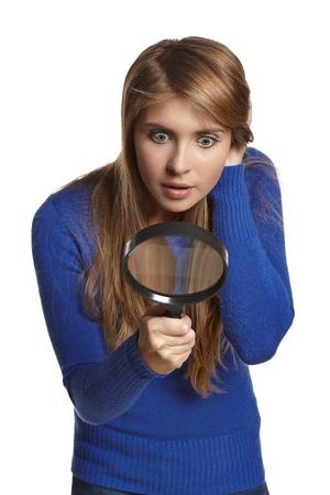 naar beneden kijken: Verbaasd meisje kijkt door het vergrootglas naar beneden, over witte achtergrond