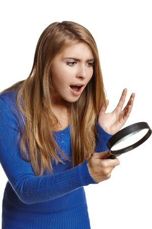 Surprised woman looking through the magnifying glass, over white background  photo