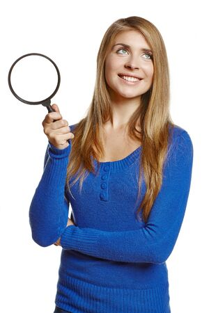 upwards: Smiling young female holding magnifying glass, isolated on white background Stock Photo