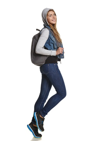 Hiking  Girl hiker with backpack in full length walking in studio photo