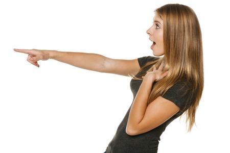 Vue de côté d'une femme désinvolte excité soulignant copyspace, sur fond blanc