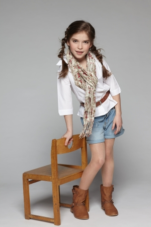 Little girl standing in full length leaning on the wooden chair photo