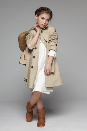 overcoat: Little girl wearing  trench coat holding handbag, over gray background