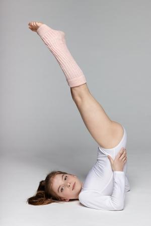 rhythmic gymnastic: Deportes deportivo Ni�os Ni�a en el suelo con las piernas en alto Foto de archivo