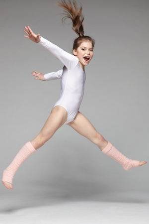 Young excited girl jumping in the studio photo
