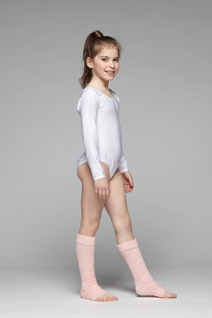 young gymnast: Smiling little girl wearing sport clothing standing in studio in full length Stock Photo