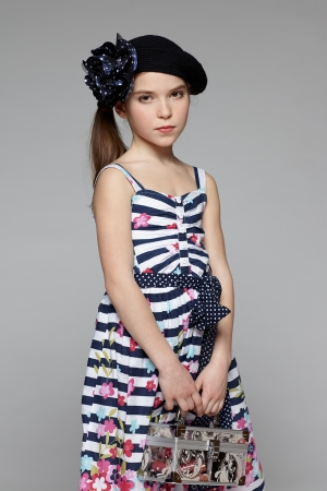 Calm little fashion girl wearing marine style dress and cap with flower holding beauty box Stock Photo - 18999864