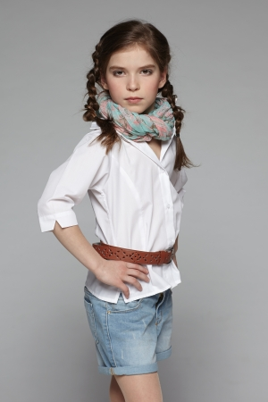 Little fashion girl posing with hands on hips photo