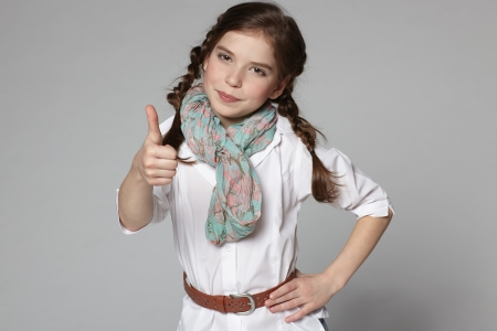 Preteen girl showing thumb up sign photo