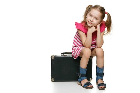 Little tourist  Little girl with sitting on the old fashioned suitcase in full length, over white background photo