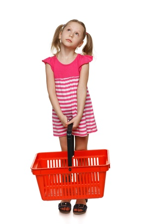 ful: Little shopper  Little girl in ful length holding empty shopping basket and looking up at blank space, over white background Stock Photo