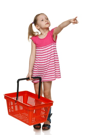 ful: Little shopper  Little girl in ful length holding empty shopping basket and pointing to the side, over white background