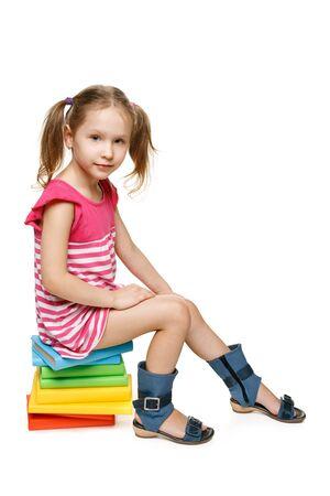 Little preschool girl sitting on the stack of books, in full length, over white background photo