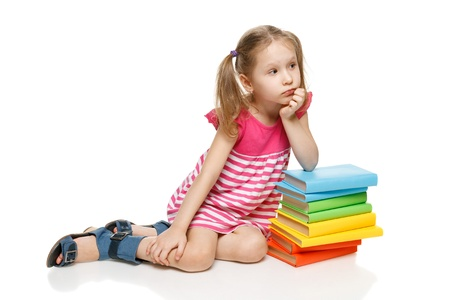 girl reading book: Little pensive girl sitting on the floor leaning on the stack of books looking away at blank copy space, over white background Stock Photo