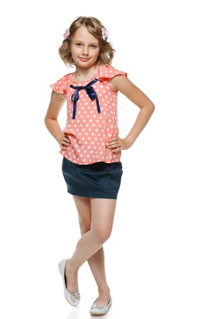 10 to 12 years: Little girl standing wiht hands on hips in full lenght, over white background