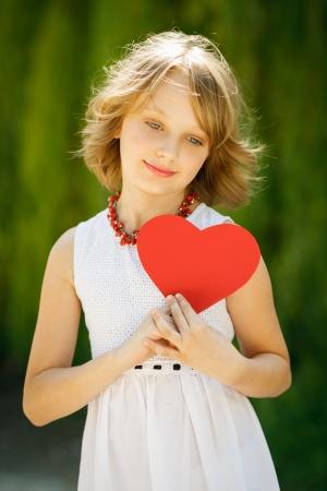 Lovely pensive girl holding heart shape outdoors Stock Photo - 19202710