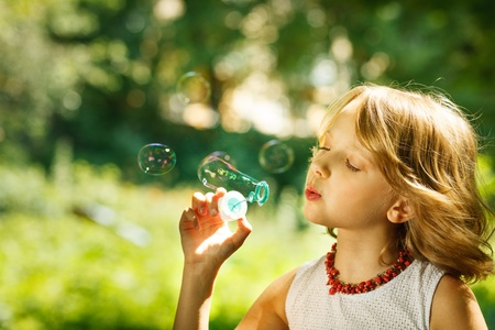 blowing bubbles: Portrait of funny lovely girl blowing soap bubbles outdoor Stock Photo