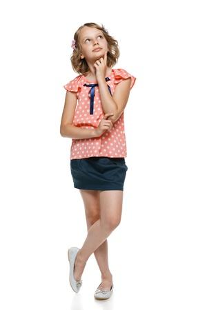 niños pensando: Longitud total de niña pensativa con el dedo en la barbilla mirando hacia arriba, sobre el blanco