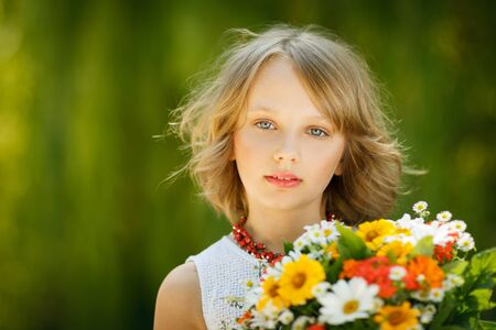 preadolescence: Girl with bunch of flowers standing outdoors over green background