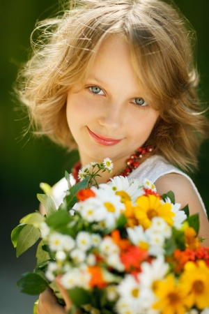 preadolescence: Smiling little girl with bunch of wildflowers standing outdoors
