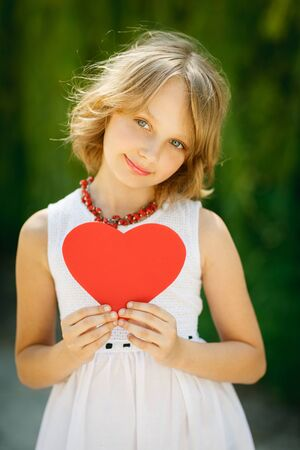 10 to 12 years: Lovely romantic girl holding heart shape outdoors