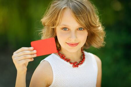 Young beautiful girl holding a blank credit card outdoor over green grass background photo