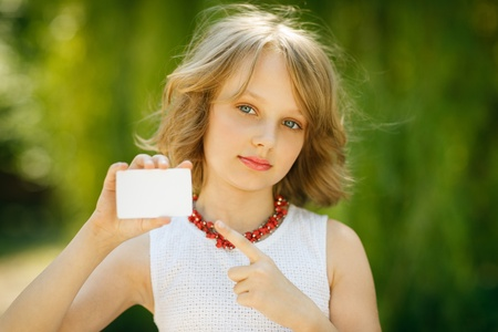 10 12 years: Girl showing blank credit card and pointing at it standing outside, over green grass background Stock Photo