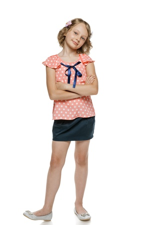 10 to 12 years: Little girl standing with folded hands in full length, over white background