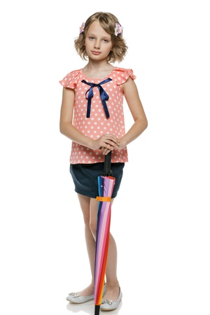Little girl standing leaning on the closed umbrella, over white background photo