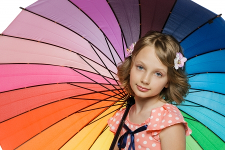 10 to 12 years: Closeup of little girl standing under colorful umbrella Stock Photo