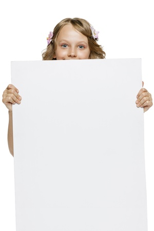 Little girl peeking from the blank banner, over white background photo