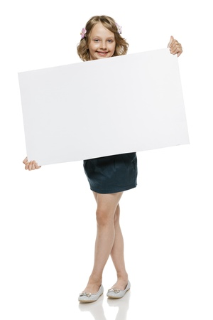 10 to 12 years: Little girl in summer clothing in full length holding blank whiteboard, isolated on white background Stock Photo