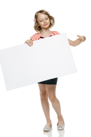 Little girl in summer clothing in full length holding blank whiteboard and pointing at it, isolated on white background photo