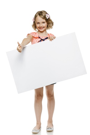 placard: Little girl in summer clothing in full length holding blank whiteboard and showing thumb up sign, isolated on white background