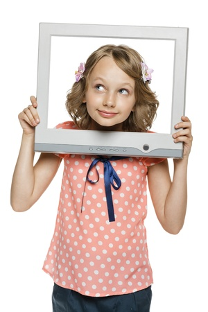 Little girl looking through the TV   computer screen frame, over white background photo