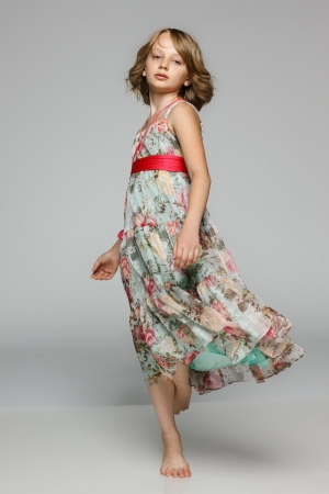 Little girl dancing in studio wearing light chiffon dress, over gray background photo