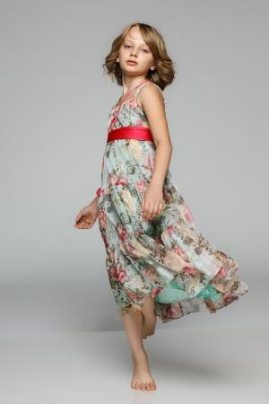 sundress: Little girl dancing in studio wearing light chiffon dress, over gray background Stock Photo