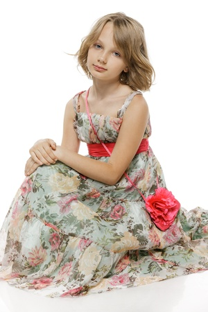 preteen: Little elegant girl wearing chiffon dress sitting on the studio floor over white background
