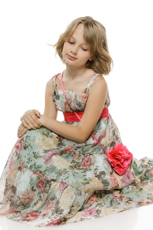 10 12 years: Little pensive girl wearing chiffon dress sitting on the studio floor looking down, over white background