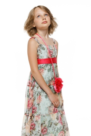 Little girl in chiffon dress looking up photo