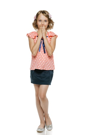 preteens girl: Surprised little girl standing with hands over mouth, over white background Stock Photo