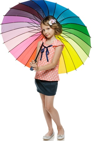 Little girl standing under colorful umbrella, over white background photo