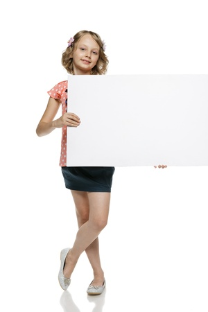 Little girl in summer clothing in full length holding blank whiteboard, isolated on white background photo