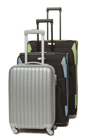 Three large travel suitcases standing over white background photo