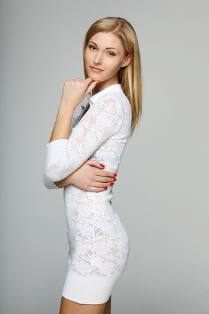 mini dress: Smiling woman in white lacy dress over gray background