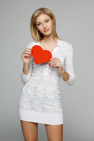 Woman in white lacy dress holding heart shape over gray background photo