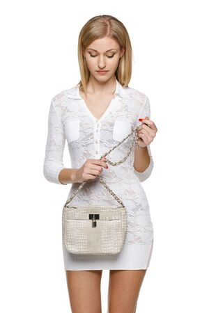 Woman holding her handbag and looking at it, over white background Stock Photo - 19203405