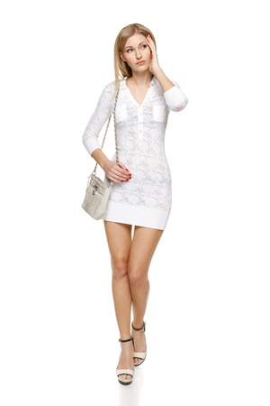 Beautiful woman in white lacy dress with small handbag in full length walking looking out of frame, over white background Stock Photo - 19203396