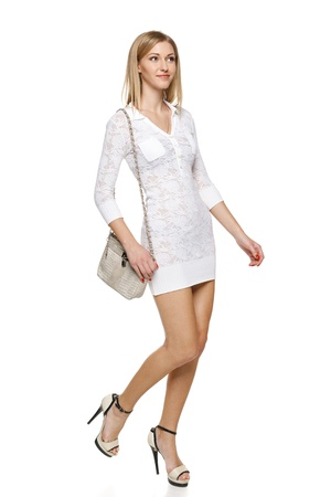 Smiling woman in white lacy dress with small handbag in full length walking over white background Stock Photo - 19203398